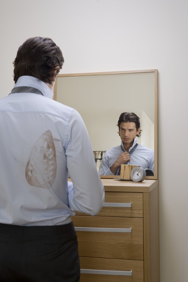 Young man adjusting tie in mirror, iron stain on shirt, rear view