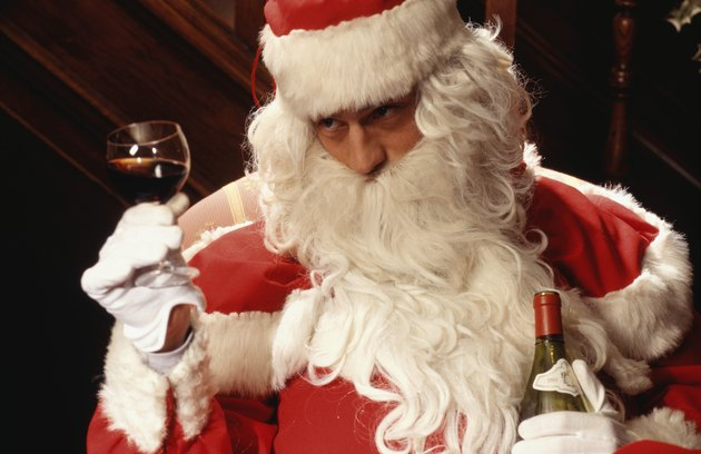 Santa Claus holding glass and bottle of wine