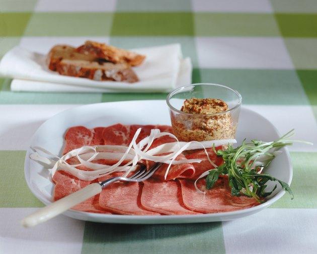 Ham with arugula leaf in plate, close-up
