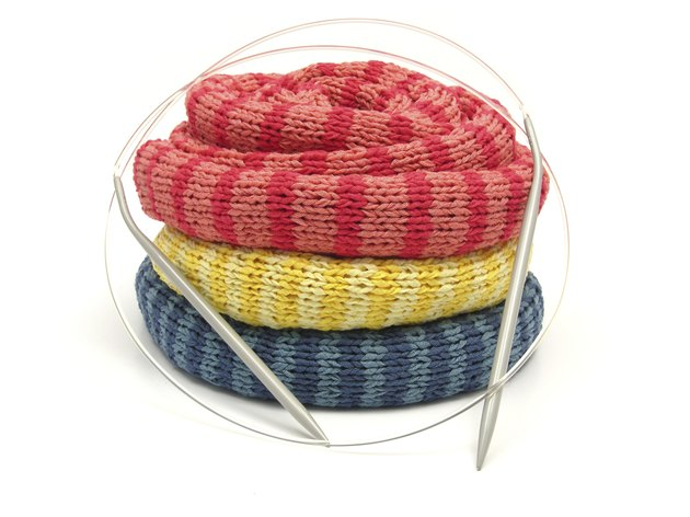 Three striped reeled up knitting scarfs on white