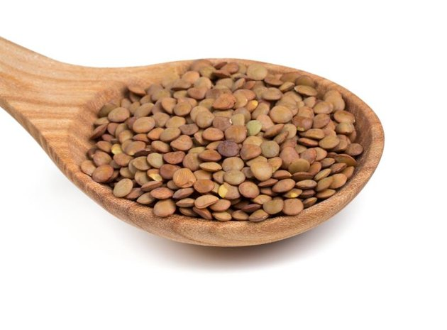 brown lentils in a wooden spoon