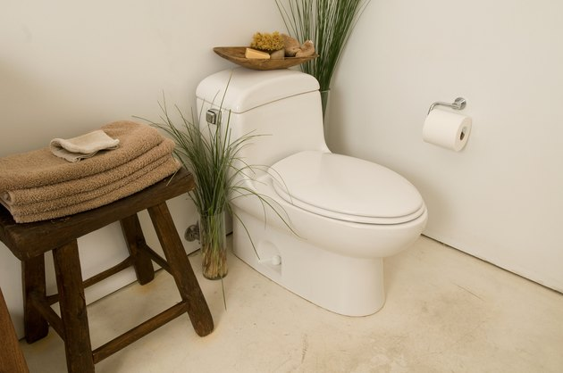 Corner of bathroom with toilet and towels on stool