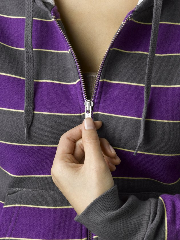 Young woman zipping purple hooded sweatshirt, close-up (full frame)
