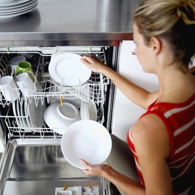 woman taking dishes out of a dishwasher