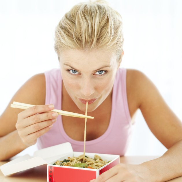 woman eating noodles from a take-out box with chopsticks