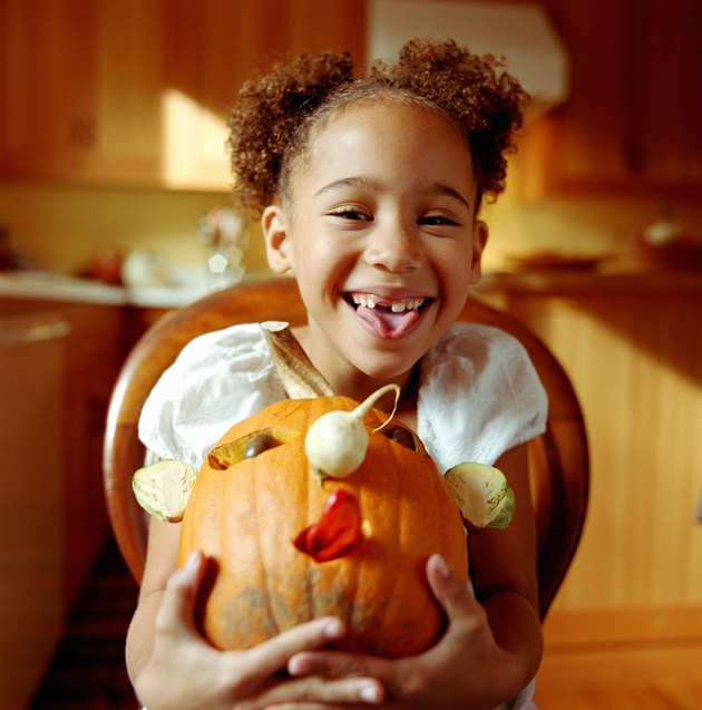 Girl (6-8) holding decorated pumpkin, smiling, portrait
