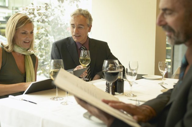 Three business people looking at menus in restaurant, close-up