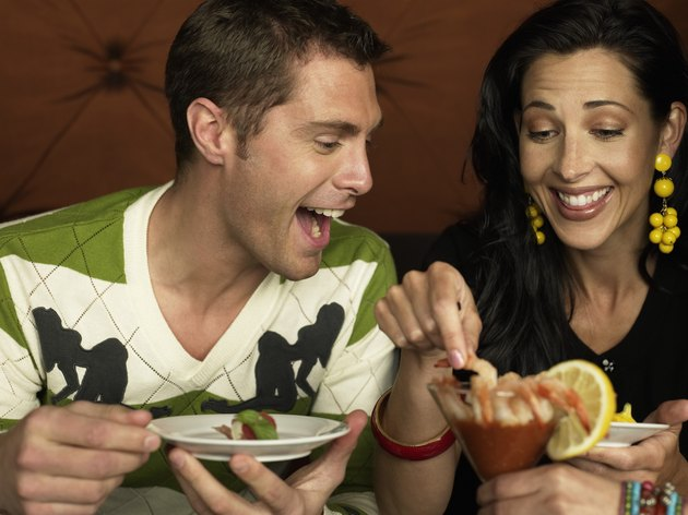 Man and woman sharing appetizers, laughing