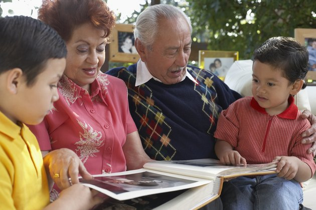 Close-up of a senior couple looking at photographs with their grandsons