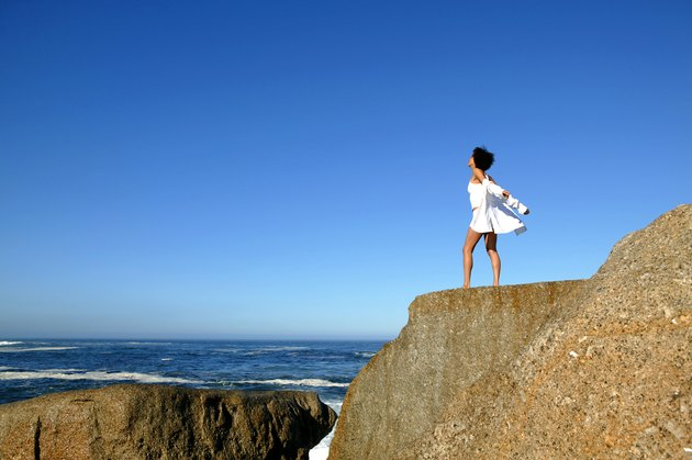 Woman standing on cliff by seashore
