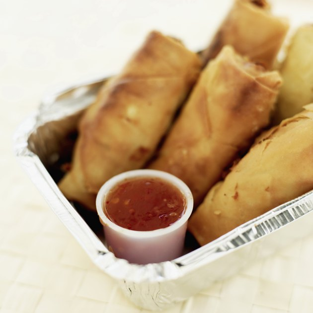 Close-up of spring rolls and sauce in a box