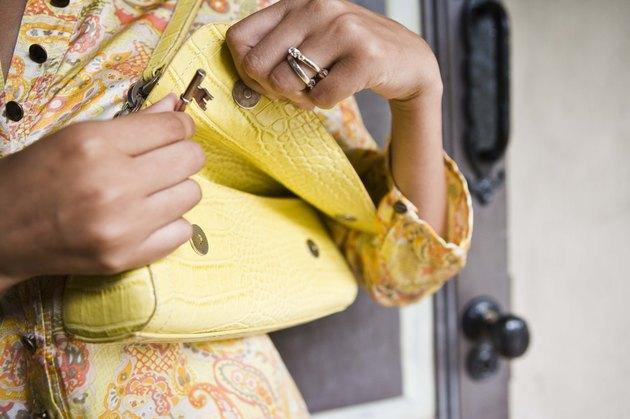 Woman opening yellow purse