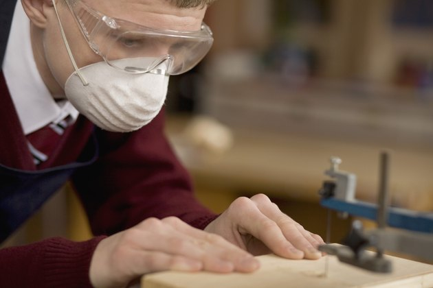 Student using jigsaw in wood shop class
