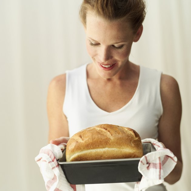 Young woman looking at a loaf of freshly baked bread