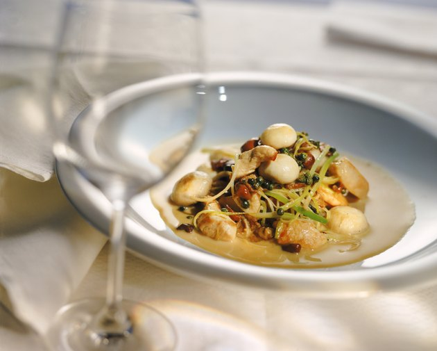 Plate of vegetable with scallops and wine glass