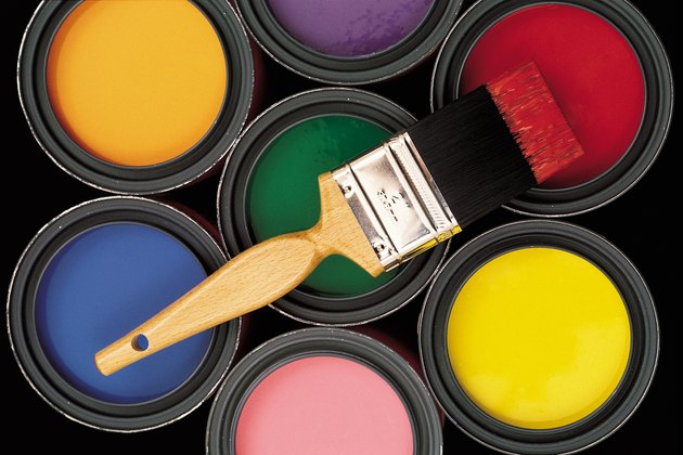 Assorted colors of paint in cans with brush