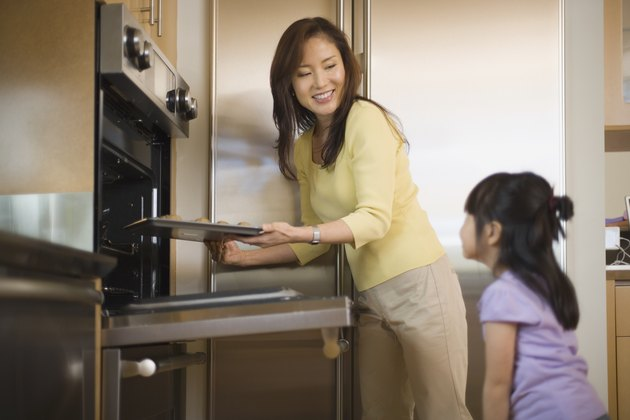 Mother putting cookies into oven with daughter
