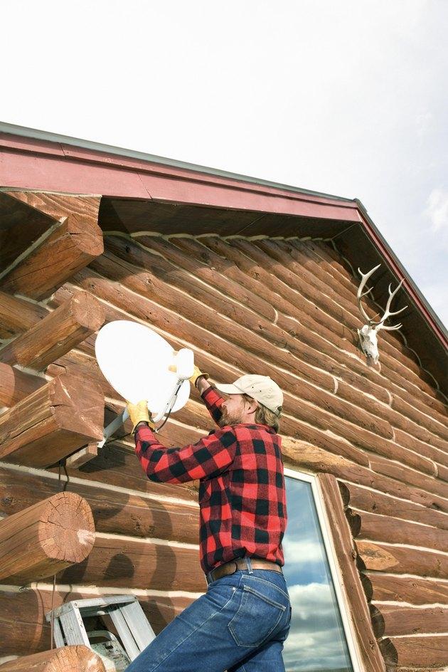 Man installing satellite dish on house