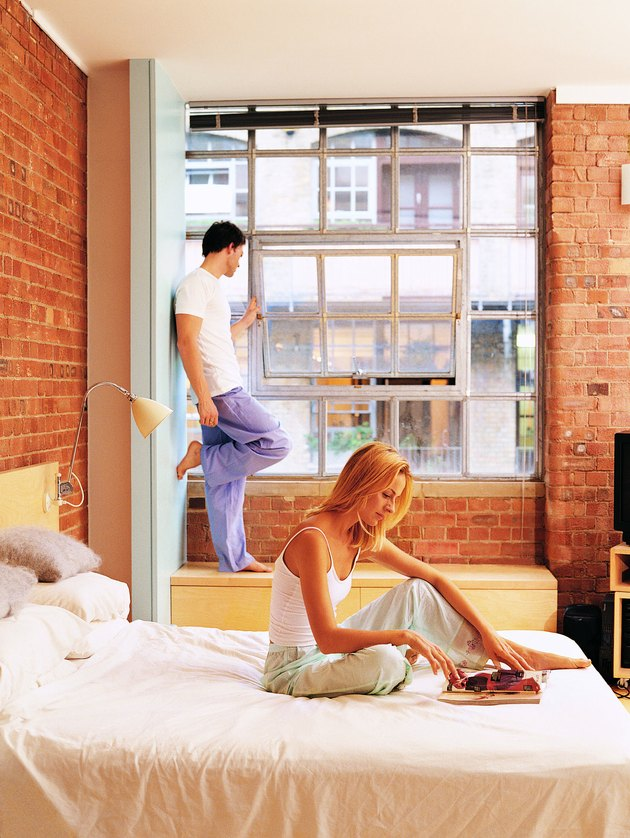 Woman Reading in Bed with a Man Looking out the Window