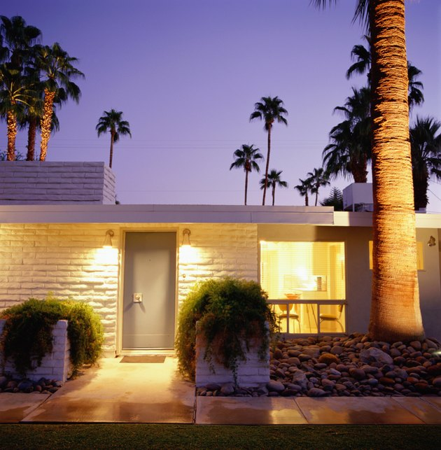 Exterior of brick home with palm trees in background