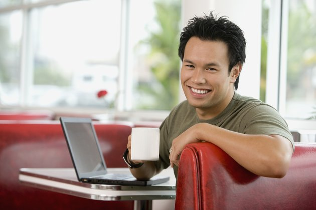 Asian man sitting in diner booth