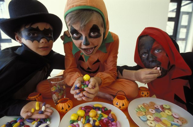 Kids dressed in Halloween costumes eating candy