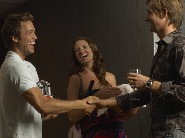Man holding pack of beers shaking another man's hand, woman laughing