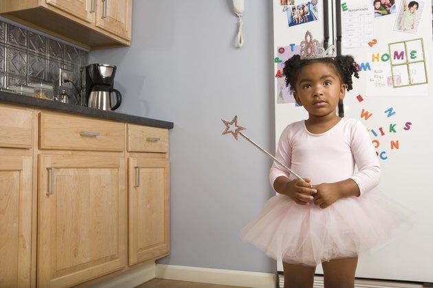Girl in ballerina costume in kitchen