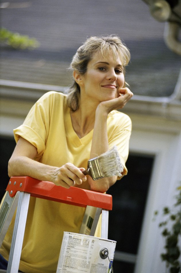 Woman posing by ladder with paintbrush
