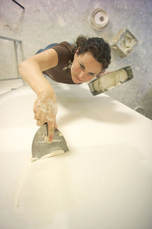 Woman applying joint compound to wall