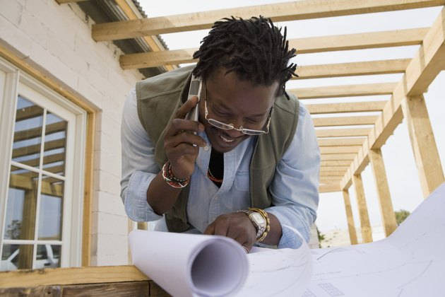 African man on cell phone looking at blueprints