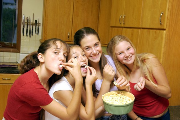 Teenage girls eating popcorn