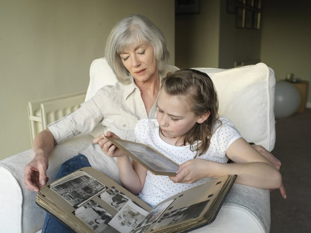 Grandmother and granddaughter (9-11) looking at photo album
