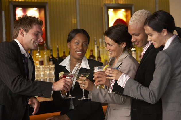 Businesspeople holding drinks in bar