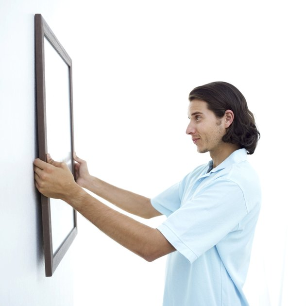 young man fixing a picture frame on the wall