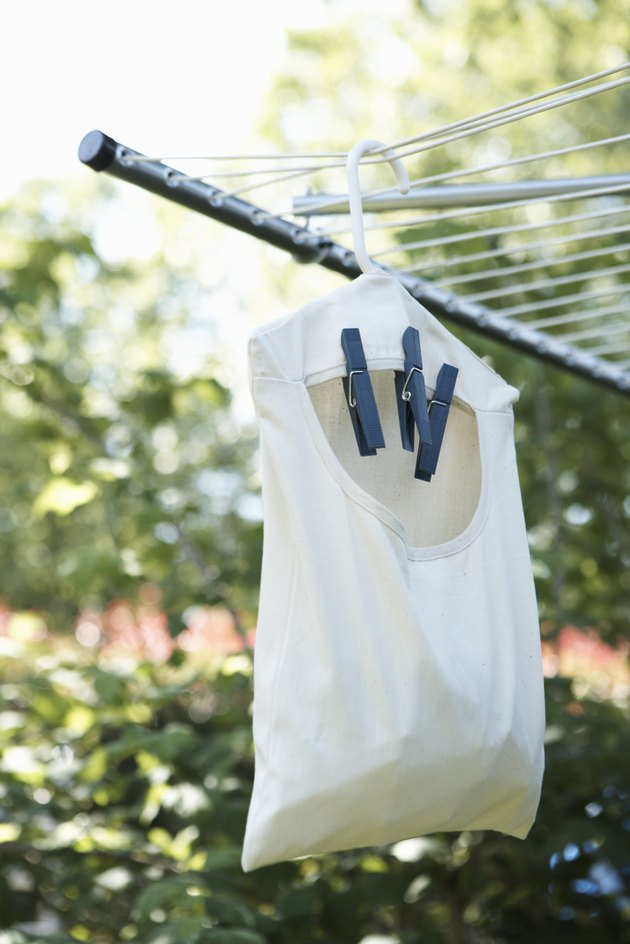 Bag of clothespins hanging from clothesline outdoors