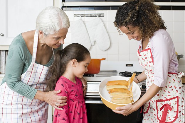 A family looking at a dish of tamales