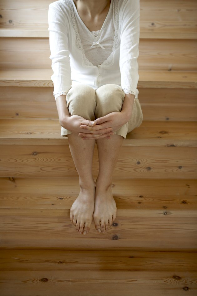 Woman with bare feet, sitting on wooden stairs in home