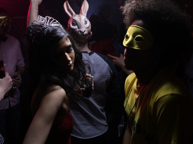 People wearing costumes, dancing in night club