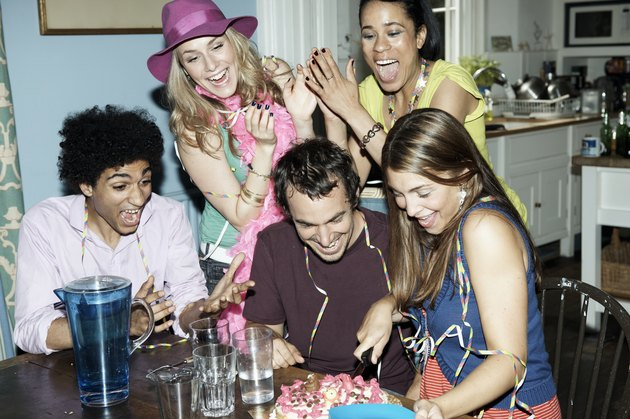 Group of friends cutting a cake