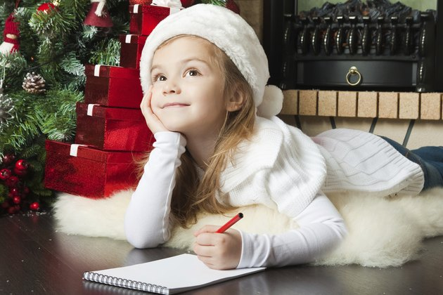 Pretty girl in Santa hat writes letter