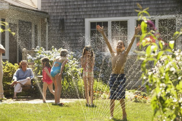 Group of four children playing around a sprinkler in a garden