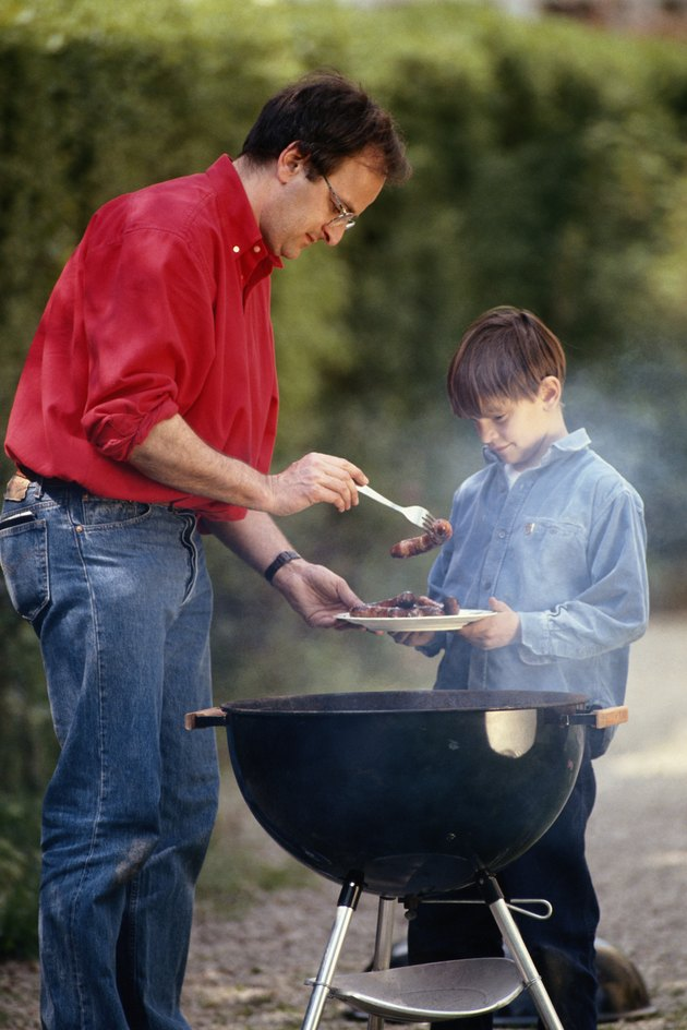 Father serving cooked food in son's (6-9) plate, outdoors
