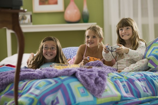 Girls playing video games at slumber party