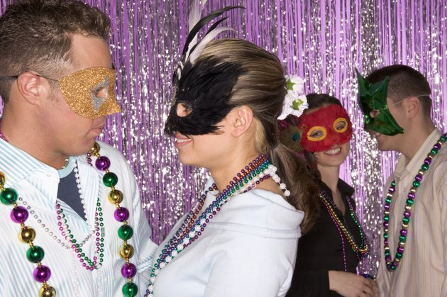 Couples dancing, wearing Mardi Gras masks and beads