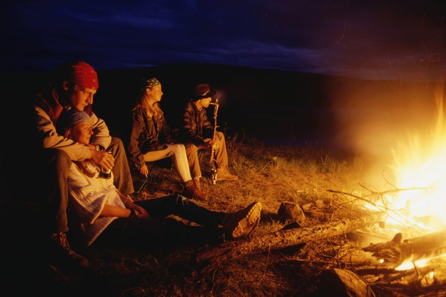 Four people sitting by open fire at night