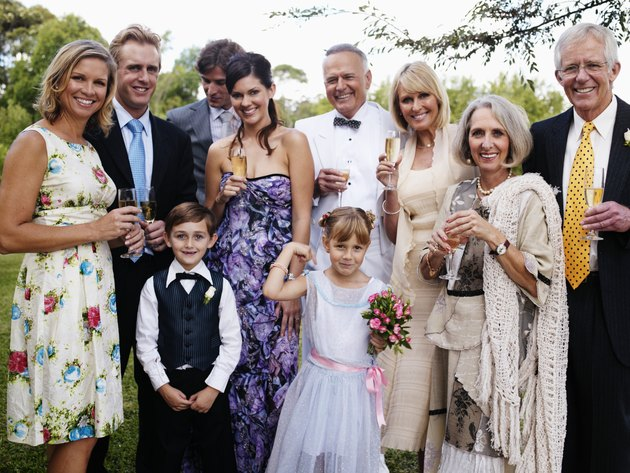 Bride and groom with wedding guests, smiling, portrait