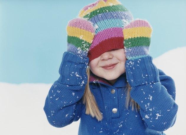 Studio Portrait of a Young Girl Hiding Under Her Woolen Hat