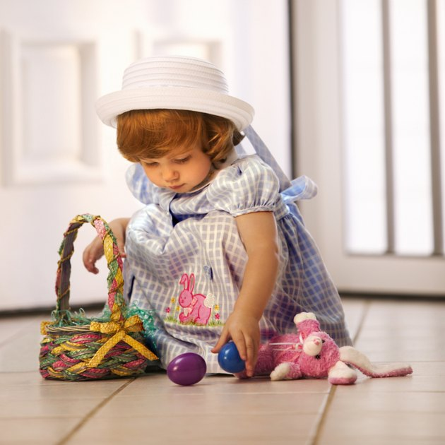 A toddler in her Easter dress plays with eggs in her basket