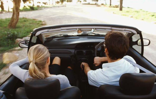 Rear view of young couple traveling in car